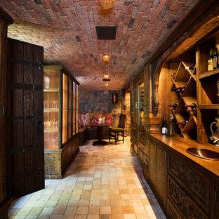 Foto på en mycket stor rustik vinkällare, med klinkergolv i terrakotta och vindisplay