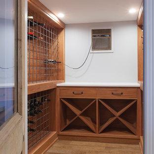 Ejemplo de bodega industrial, de tamaño medio, con suelo laminado, botelleros y suelo marrón