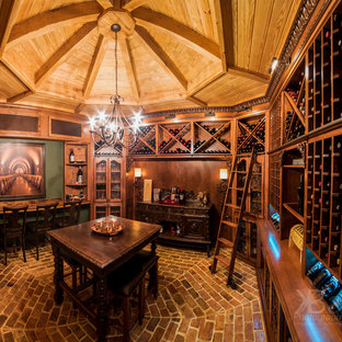 Mediterranean wine cellar in Jacksonville with brick flooring and cube storage.