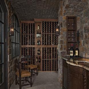 Inspiration pour une cave à vin traditionnelle avec des casiers et un sol gris.