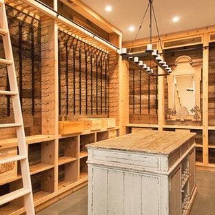 Lantlig inredning av en stor vinkällare, med betonggolv, vindisplay och grått golv