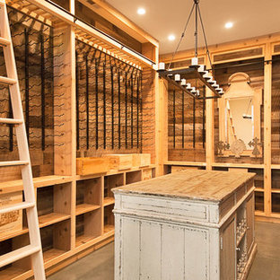 Photo of a large rural wine cellar in San Francisco with concrete flooring, display racks and grey floors.