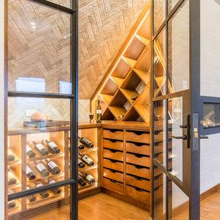 Imagen de bodega contemporánea, de tamaño medio, con suelo de madera en tonos medios y botelleros de rombos
