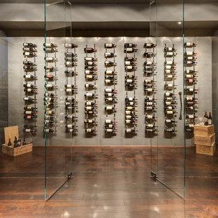 Inspiration för mellanstora moderna vinkällare, med mellanmörkt trägolv, vinhyllor och brunt golv