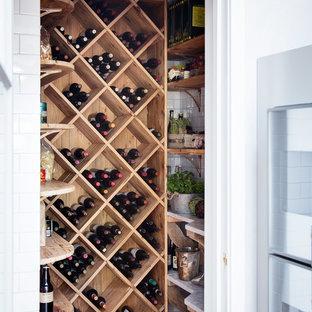 Inspiration för en liten lantlig vinkällare, med mörkt trägolv, vinställ med diagonal vinförvaring och brunt golv