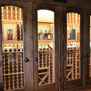 Exempel på en mellanstor amerikansk vinkällare, med mörkt trägolv, vinhyllor och brunt golv