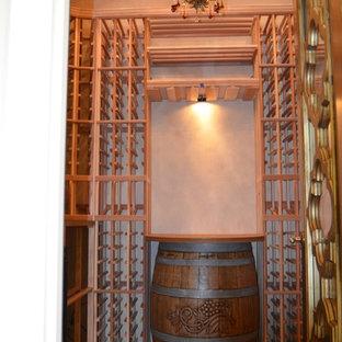 Cette image montre une cave à vin traditionnelle de taille moyenne avec un sol en bois brun et des casiers.