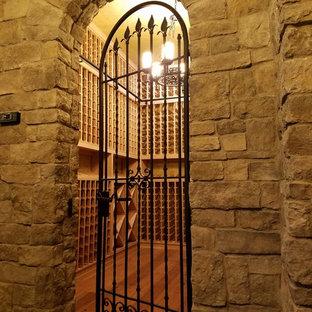 Idée de décoration pour une cave à vin tradition de taille moyenne avec des casiers, un sol en bois brun et un sol beige.