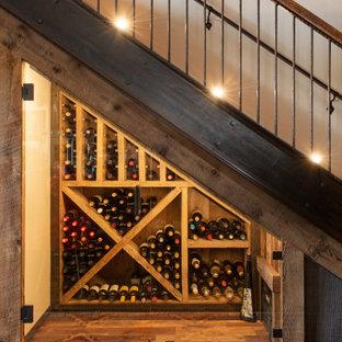 Inredning av en rustik mellanstor vinkällare, med mellanmörkt trägolv, vinställ med diagonal vinförvaring och brunt golv