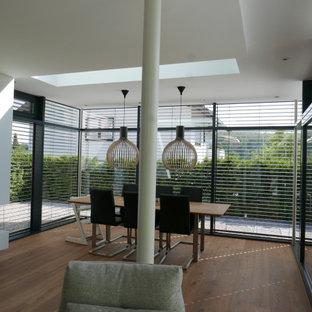 Idéer för ett stort modernt uterum, med mellanmörkt trägolv, en dubbelsidig öppen spis, en spiselkrans i gips, takfönster och brunt golv