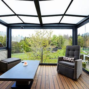 Imagen de galería minimalista, de tamaño medio, con suelo de madera oscura, estufa de leña, techo de vidrio y suelo multicolor