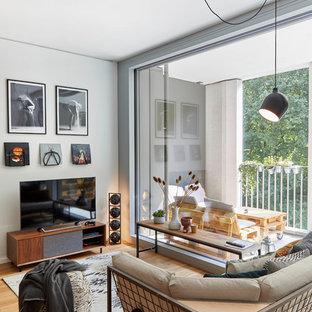 Modernes Wohnzimmer mit weißer Wandfarbe, braunem Holzboden, freistehendem TV und braunem Boden in München