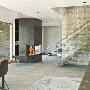 Ejemplo de salón para visitas abierto, contemporáneo, extra grande, sin televisor, con estufa de leña, marco de chimenea de metal, paredes beige, suelo de piedra caliza y suelo beige