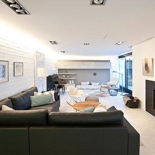 Immagine di un grande soggiorno nordico aperto con sala formale, pareti bianche, pavimento in gres porcellanato, camino classico, cornice del camino piastrellata e TV nascosta