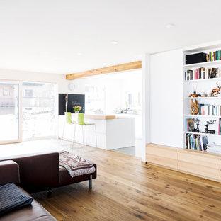 Große, Offene Nordische Bibliothek ohne Kamin mit weißer Wandfarbe, braunem Holzboden und braunem Boden in Sonstige