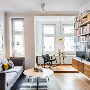 Nordische Bibliothek ohne Kamin mit weißer Wandfarbe, braunem Holzboden und freistehendem TV in Köln