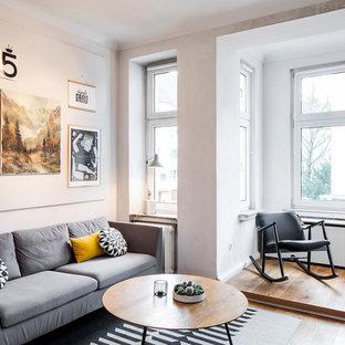 Mittelgroßes, Abgetrenntes Nordisches Wohnzimmer ohne Kamin mit weißer Wandfarbe, braunem Holzboden und braunem Boden in Köln
