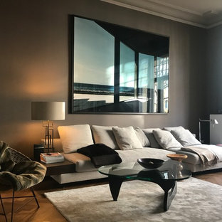 Ejemplo de sala de estar cerrada, actual, pequeña, con paredes marrones, estufa de leña, marco de chimenea de metal, suelo de madera en tonos medios y suelo marrón