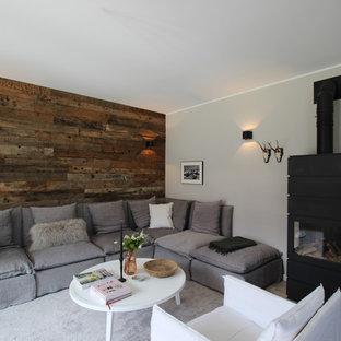 Modelo de sala de estar cerrada, rústica, de tamaño medio, sin televisor, con paredes grises, estufa de leña y suelo beige