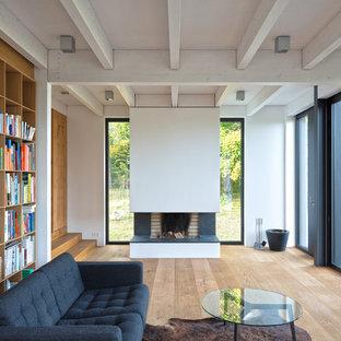 Abgetrennte, Mittelgroße Moderne Bibliothek mit weißer Wandfarbe, braunem Holzboden, Kamin und braunem Boden in Hamburg
