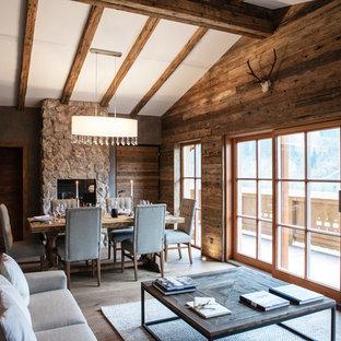 Großes, Fernseherloses, Offenes Uriges Wohnzimmer mit brauner Wandfarbe, hellem Holzboden, Kamin, Kaminumrandung aus Stein und braunem Boden in München