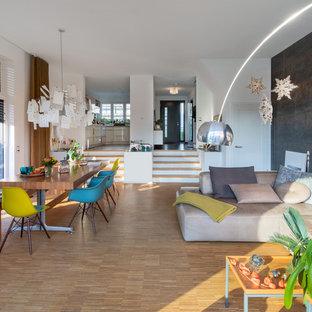 Offenes Modernes Wohnzimmer mit weißer Wandfarbe, braunem Holzboden und braunem Boden in Essen