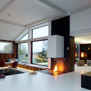 Ejemplo de salón para visitas tipo loft, de estilo zen, grande, sin televisor, con paredes marrones, suelo de cemento, chimenea lineal, marco de chimenea de metal y suelo blanco