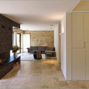 Imagen de salón abierto, moderno, con paredes multicolor, suelo de travertino, chimenea tradicional, marco de chimenea de ladrillo y suelo beige