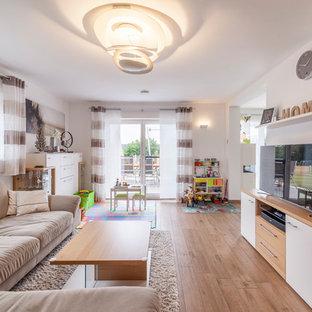 Mittelgroßes, Offenes Modernes Wohnzimmer ohne Kamin mit weißer Wandfarbe, braunem Holzboden, freistehendem TV und braunem Boden in Sonstige