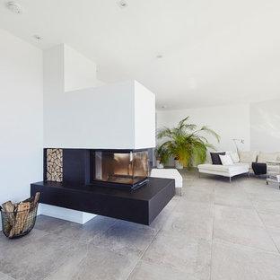 Mittelgroßes, Offenes Modernes Wohnzimmer mit weißer Wandfarbe, Schieferboden, Kamin, verputzter Kaminumrandung und grauem Boden in Essen