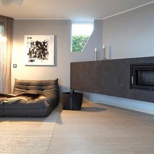 Esempio di un grande soggiorno contemporaneo aperto con pareti grigie, pavimento in travertino, camino sospeso, cornice del camino in intonaco, pavimento beige, libreria e nessuna TV