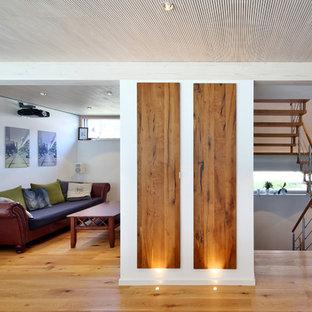 Kleines, Repräsentatives, Offenes Modernes Wohnzimmer ohne Kamin mit weißer Wandfarbe, braunem Holzboden und braunem Boden in München