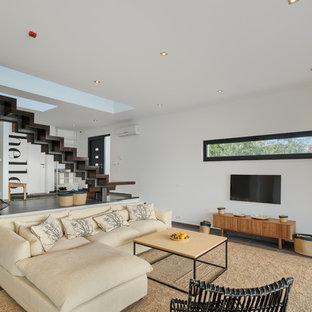 Geräumiges, Offenes Modernes Wohnzimmer mit weißer Wandfarbe, braunem Holzboden, Gaskamin, verputztem Kaminsims, Wand-TV und braunem Boden in München