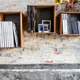 他の地域の広い北欧スタイルのおしゃれなリビングロフト (ライブラリー、茶色い壁、無垢フローリング、吊り下げ式暖炉、タイルの暖炉まわり、テレビなし、オレンジの床) の写真
