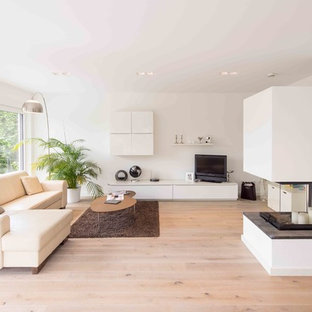 Mittelgroßes Modernes Wohnzimmer mit weißer Wandfarbe, hellem Holzboden, Kaminofen, verputzter Kaminumrandung, freistehendem TV und braunem Boden in Sonstige