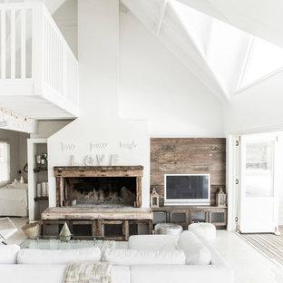 他の地域の中サイズのビーチスタイルのおしゃれなLDK (白い壁、淡色無垢フローリング、標準型暖炉、木材の暖炉まわり、壁掛け型テレビ) の写真