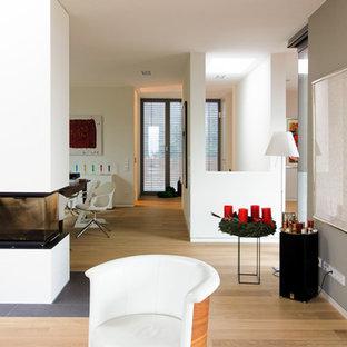 Esempio di un soggiorno minimal aperto con sala formale, pareti bianche, parquet chiaro, camino bifacciale e cornice del camino in intonaco