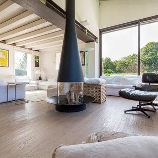 Foto di un grande soggiorno contemporaneo aperto con pareti bianche, parquet chiaro, camino bifacciale, cornice del camino in metallo e pavimento beige