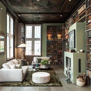 Fernseherlose, Große Moderne Bibliothek im Loft-Stil mit grüner Wandfarbe, verputztem Kaminsims, Gaskamin und grauem Boden in Hamburg