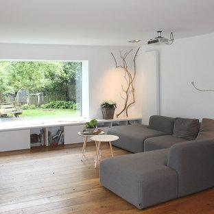 Неиссякаемый источник вдохновения для домашнего уюта: гостиная комната среднего размера в скандинавском стиле с белыми стенами и паркетным полом среднего тона без камина