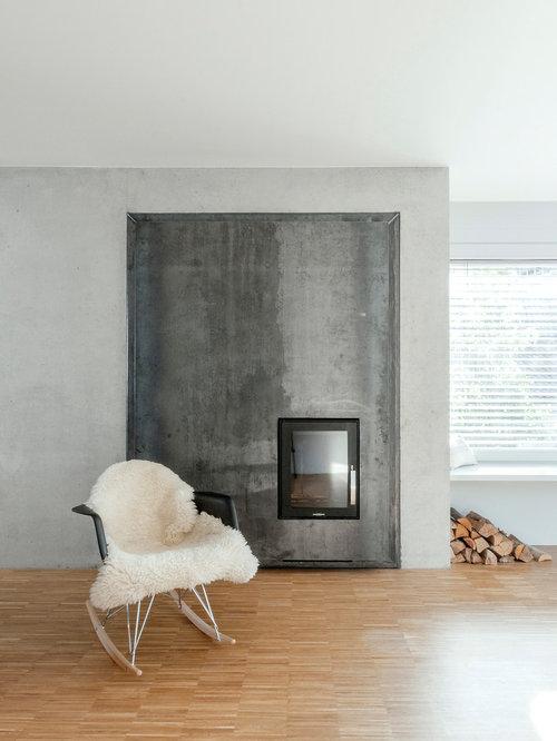 Nordisches Wohnzimmer Mit Grauer Wandfarbe, Braunem Holzboden, Kamin,  Kaminsims Aus Metall Und Braunem