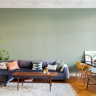 Eclectic open plan living room in Berlin with green walls and brown floors.
