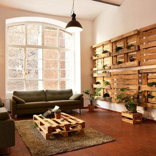 Ejemplo de sala de estar tipo loft, industrial, de tamaño medio, sin chimenea y televisor, con paredes blancas y suelo rojo