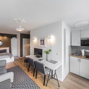Immagine di un piccolo soggiorno nordico aperto con pareti grigie, pavimento in legno massello medio, nessun camino e TV autoportante