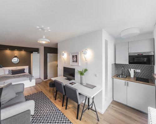 Kleines, Offenes Nordisches Wohnzimmer Ohne Kamin Mit Grauer Wandfarbe,  Braunem Holzboden Und Freistehendem TV