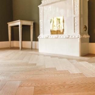 Ejemplo de salón machihembrado, de estilo de casa de campo, con suelo de madera clara y estufa de leña