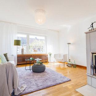 Mittelgroßes, Repräsentatives, Fernseherloses, Abgetrenntes Modernes Wohnzimmer mit weißer Wandfarbe, braunem Holzboden, Kamin, gefliestem Kaminsims und braunem Boden in Sonstige