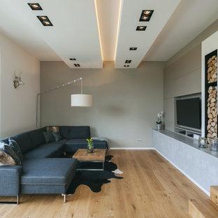 Abgetrenntes, Mittelgroßes Modernes Wohnzimmer mit beiger Wandfarbe, hellem Holzboden, Kamin, verputztem Kaminsims, Multimediawand und beigem Boden in Dortmund