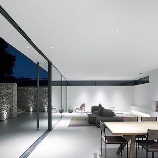 Großes, Repräsentatives Modernes Wohnzimmer im Loft-Stil mit weißer Wandfarbe, Porzellan-Bodenfliesen, verputzter Kaminumrandung, freistehendem TV und grauem Boden in Hannover