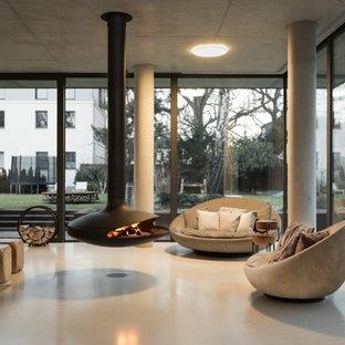 ベルリンの大きいインダストリアルスタイルのおしゃれなファミリールーム (リノリウムの床、吊り下げ式暖炉、グレーの床) の写真